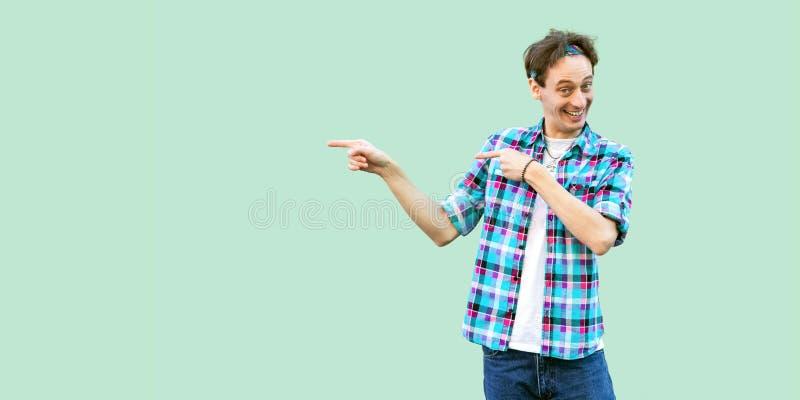 Het portret van de gelukkige grappige jonge mens in toevallig blauw geruit overhemd en hoofdband die zich met toothy glimlach bev royalty-vrije stock fotografie