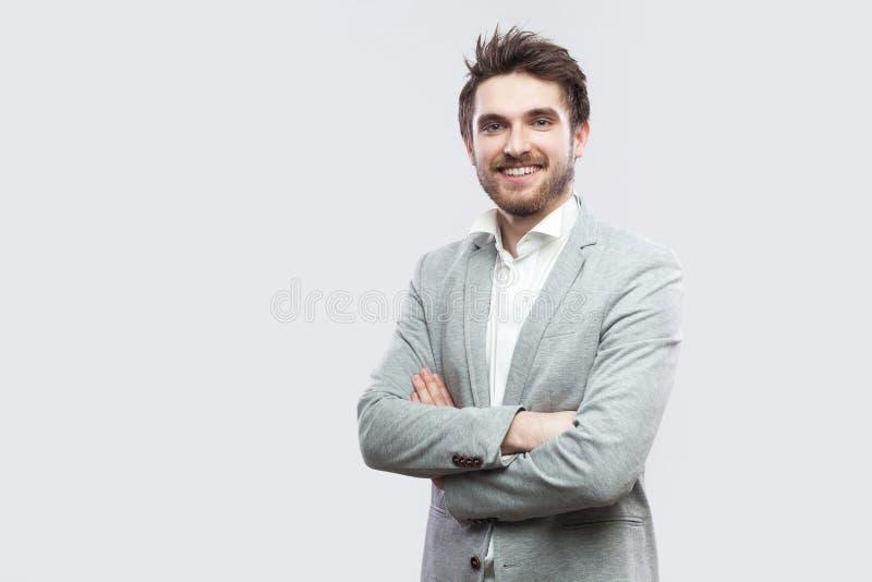 Het portret van de gelukkige tevreden knappe gebaarde mens in wit overhemd, toevallig grijs kostuum die, kruiste handen en het be royalty-vrije stock foto