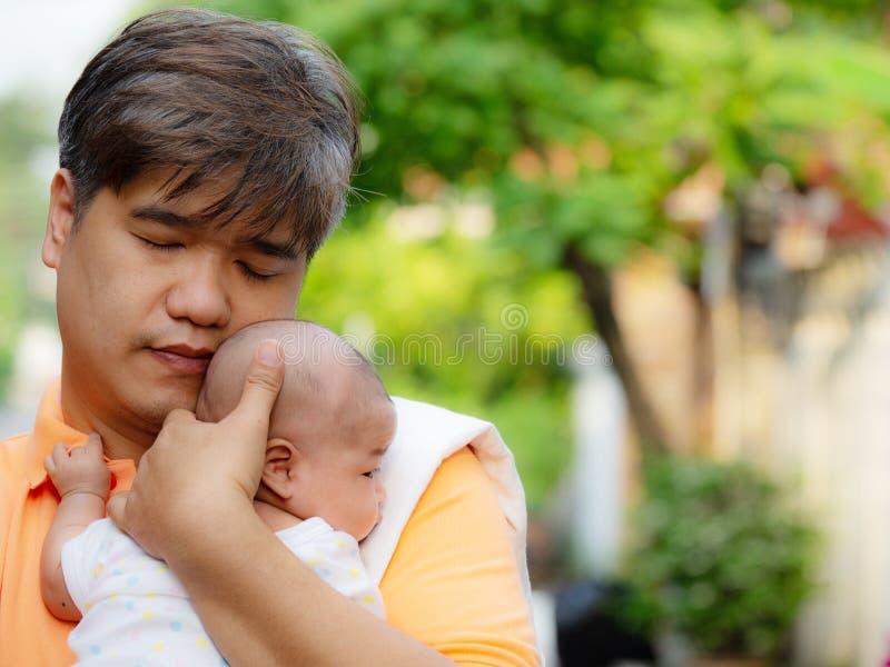 Het portret van de gelukkige vader die van Azië zijn pasgeboren zoete baby houden kleedde zich in witte kleren De vader die zijn  royalty-vrije stock afbeelding