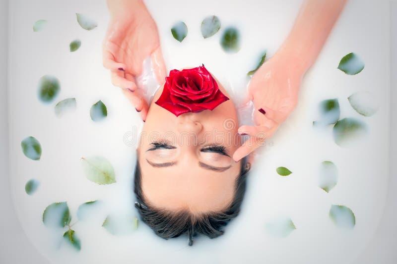 Het portret van de glamourclose-up in melkbad met en bladeren nam bloemblaadjes toe stock foto