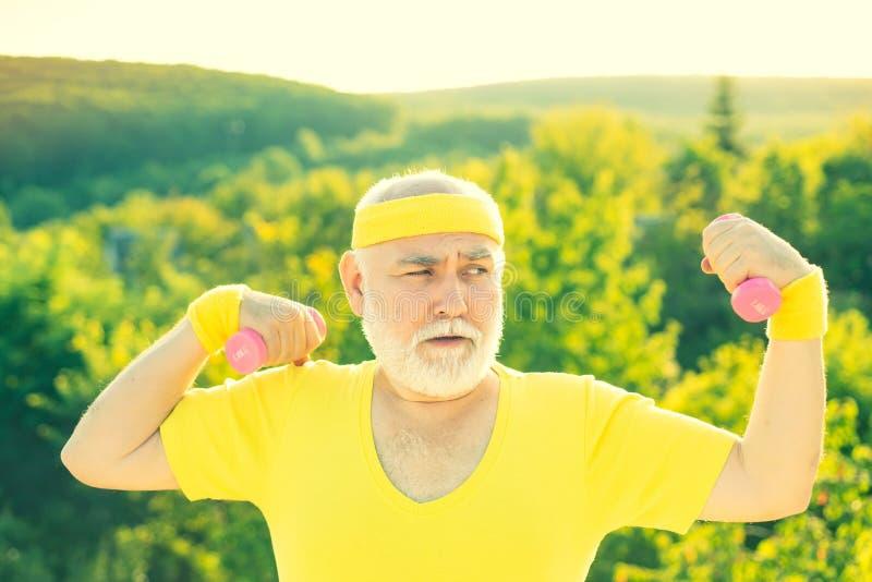 Het portret van de grootvadersportman Het hogere sportman uitoefenen met het opheffen van domoor op groene parkachtergrond stock foto
