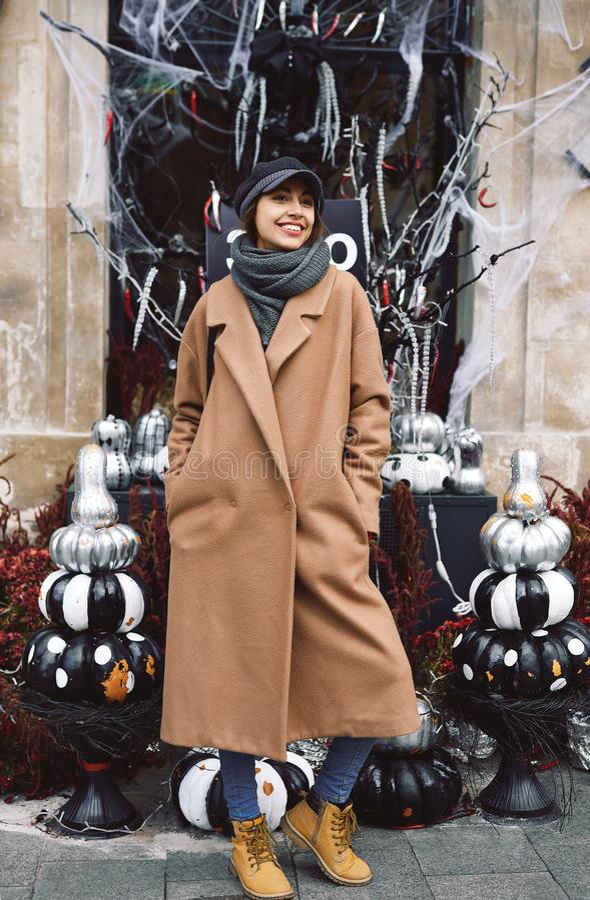Het portret van de de herfstlevensstijl van mooie glimlachende vrouw in beige laag, warme sjaal en hoed op de straat met Hallowee royalty-vrije stock foto's