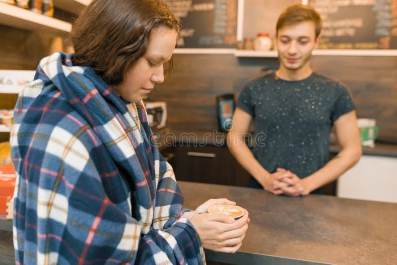 Het portret van de de herfstwinter van jong tienermeisje met kop van koffie en behandelde wollen plaiddeken in koffiewinkel royalty-vrije stock afbeelding