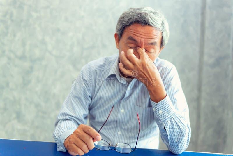 Het portret van de hogere mens is hoofdpijn en het hebben van pijn zijn sinus, hij stock foto's