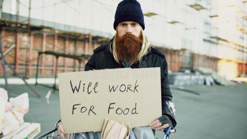 Het portret van de jonge dakloze mens die met karton camera bekijken en wil voor voedsel werken die zich dichtbij boodschappenwag royalty-vrije stock foto's