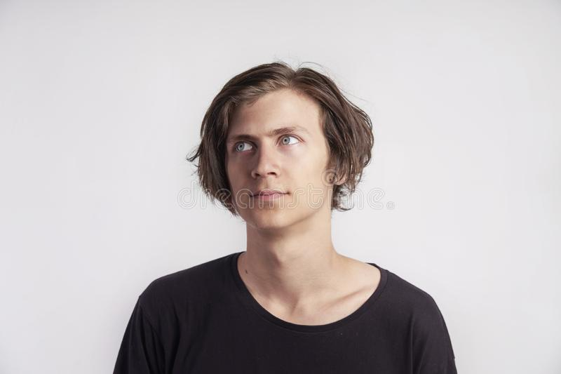 Het portret van de jonge knappe hipstermens kijkt verraste teleurstelling, zwarte t-shirt, witte achtergrond royalty-vrije stock afbeelding