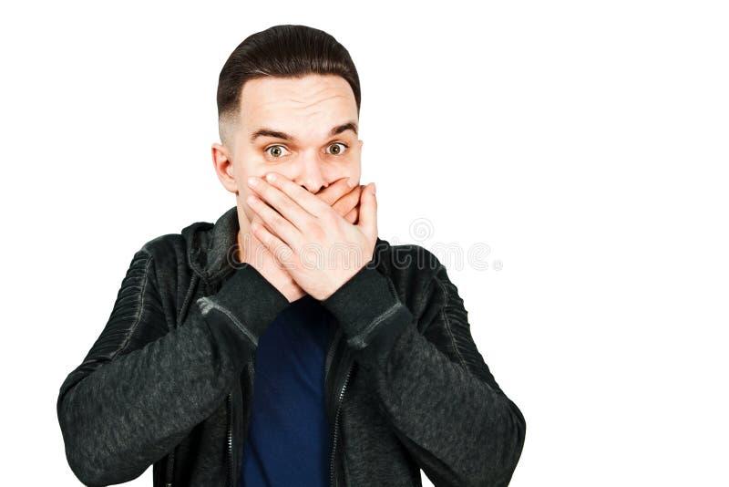 Het portret van de jonge mens deed schrikken en sluit mondhanden Ge?soleerdj op witte achtergrond stock afbeelding