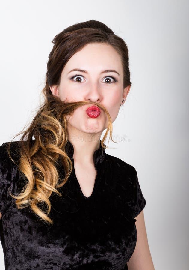 Het portret van de jonge vrouw met verschillende gelukkige emoties zij maakte van haar haar zelf snor royalty-vrije stock foto