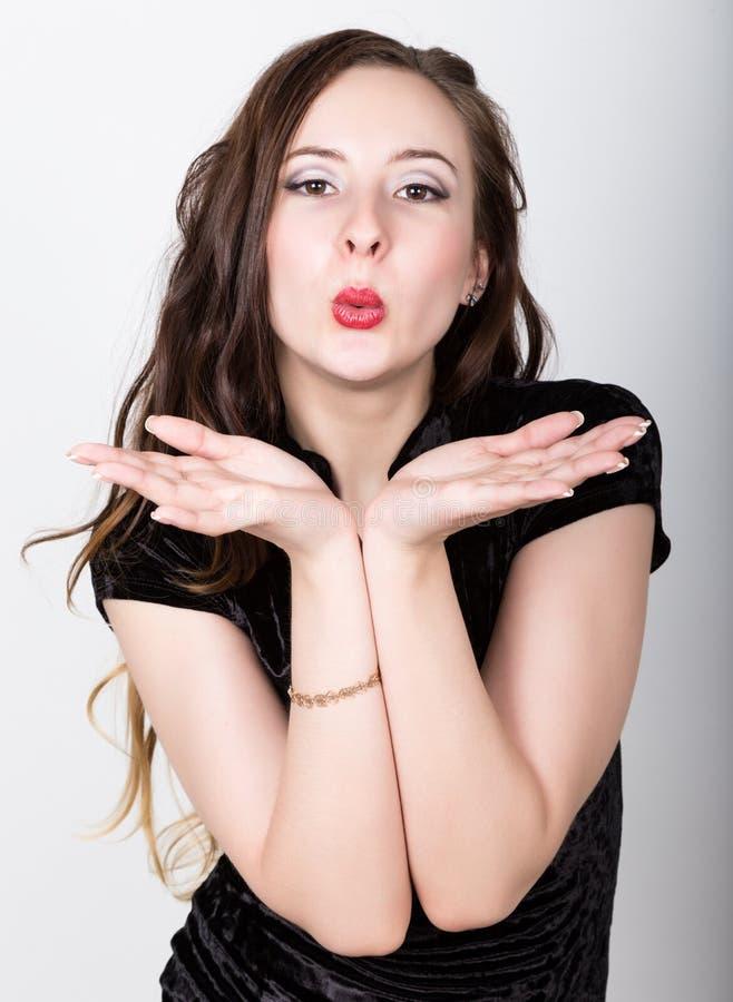 Het portret van de jonge vrouw met verschillende gelukkige emoties zij nam zijn hoofd met zijn handen Verzendt een kus royalty-vrije stock fotografie