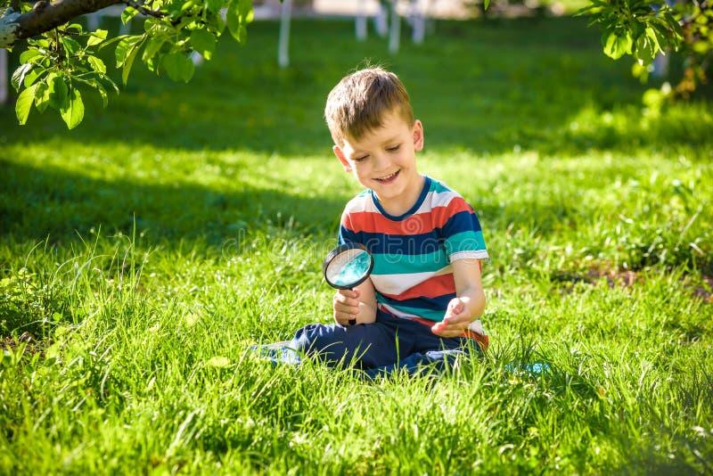 Het portret van de jongen in een tuin, overweegt installaties door een magn stock foto's