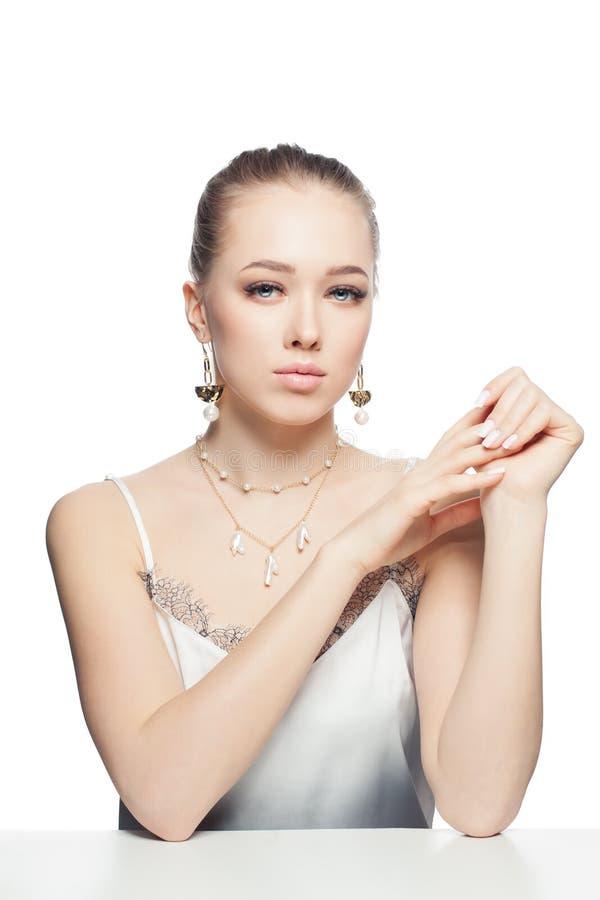 Het portret van de juwelenvrouw De vrouw van Nice met gouden die halsband en oorringen met parels op witte achtergrond worden geï royalty-vrije stock foto's
