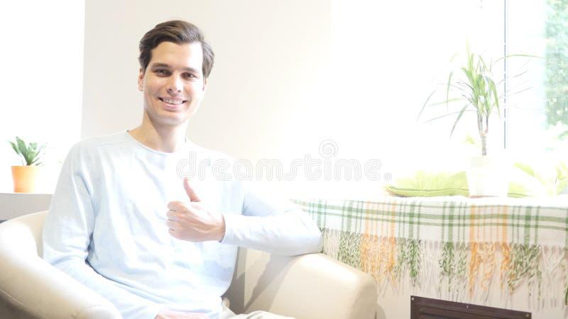 Het portret van de knappe jonge mens beduimelt omhoog het glimlachen bij camera, het werkplaats stock foto