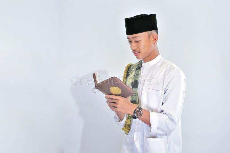 Het portret van de knappe jonge moslimmens geniet van lezend tilawat ul quran een heilige Quran in Ramadan stock afbeelding