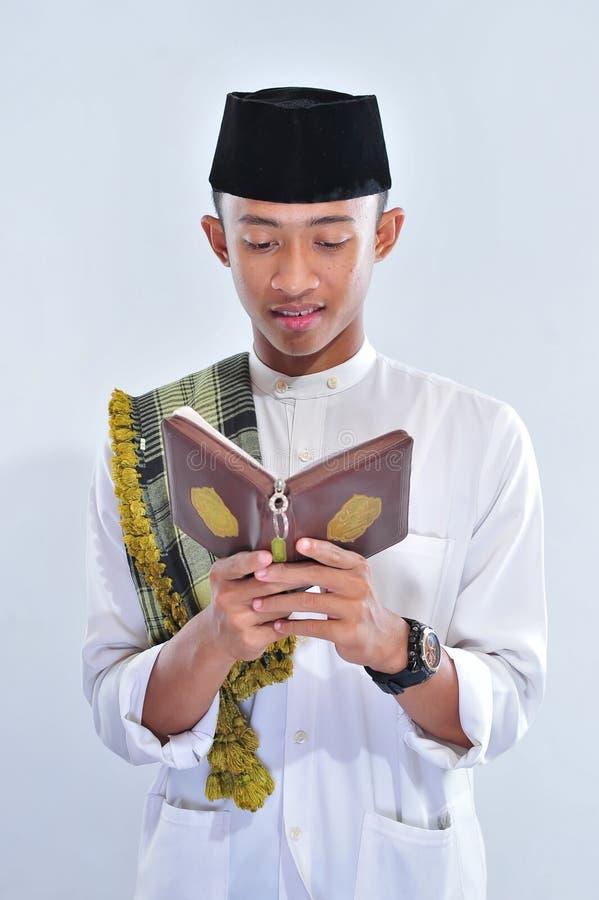 Het portret van de knappe jonge moslimmens geniet van lezend tilawat ul quran een heilige Quran in Ramadan royalty-vrije stock afbeeldingen