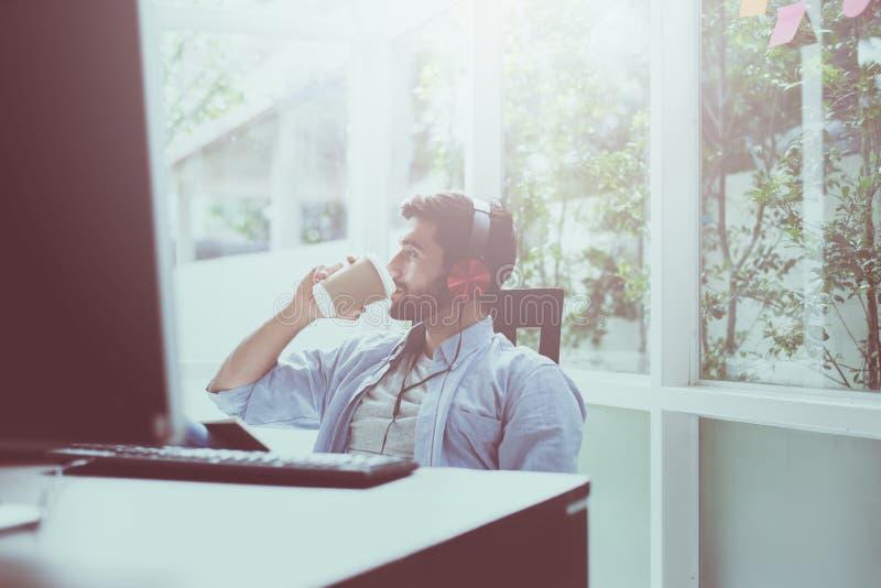 Het portret van de knappe mens met baard het drinken koffie en het luisteren aan muziek online bij modern huis, Gelukkig en het g stock afbeelding