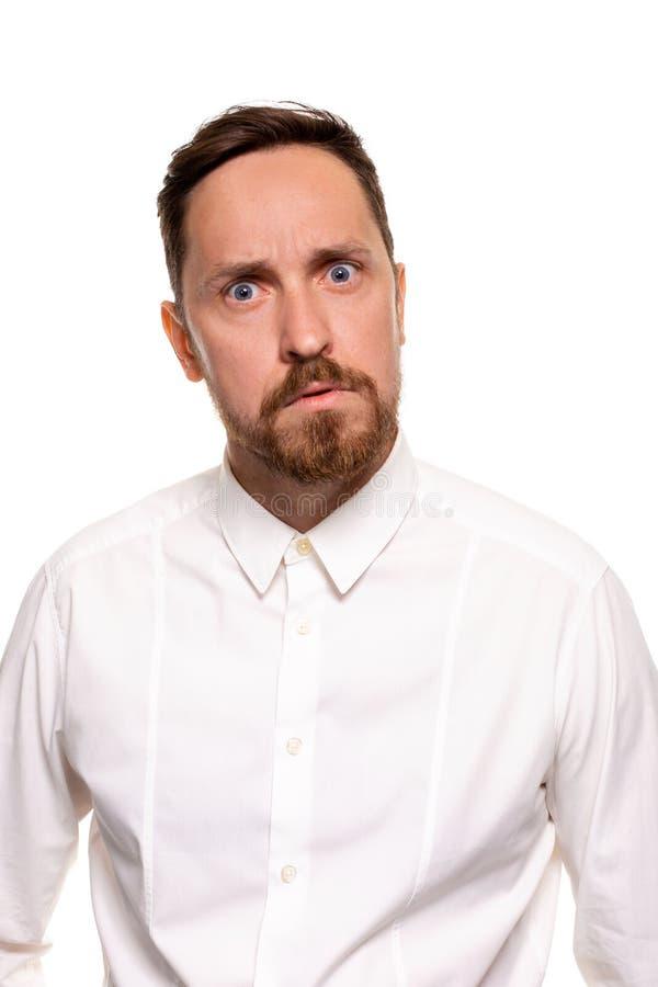 Het portret van de knappe mens met stoppelveld heeft verontwaardigde uitdrukking, frowns gezicht, gekleed in wit die overhemd, ov stock foto