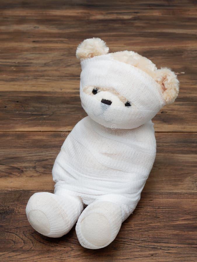 Het portret van de leuke pop van de brijteddybeer bindt met wit gaas of verband op donkere houten achtergrond stock afbeelding