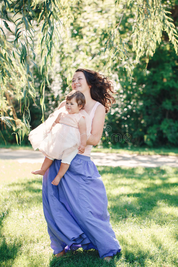 Het portret van de levensstijlgroep van glimlachende witte Kaukasische donkerbruine moederholding die dochter in het roze kleding stock afbeeldingen
