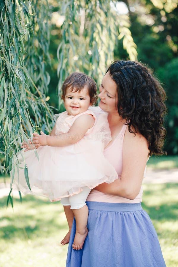 Het portret van de levensstijlgroep van glimlachende witte Kaukasische donkerbruine moederholding die dochter in roze kleding koe stock foto