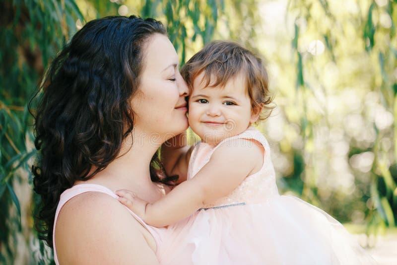 Het portret van de levensstijlgroep van mooie witte Kaukasische donkerbruine moederholding die dochter die in roze kleding koeste stock foto's