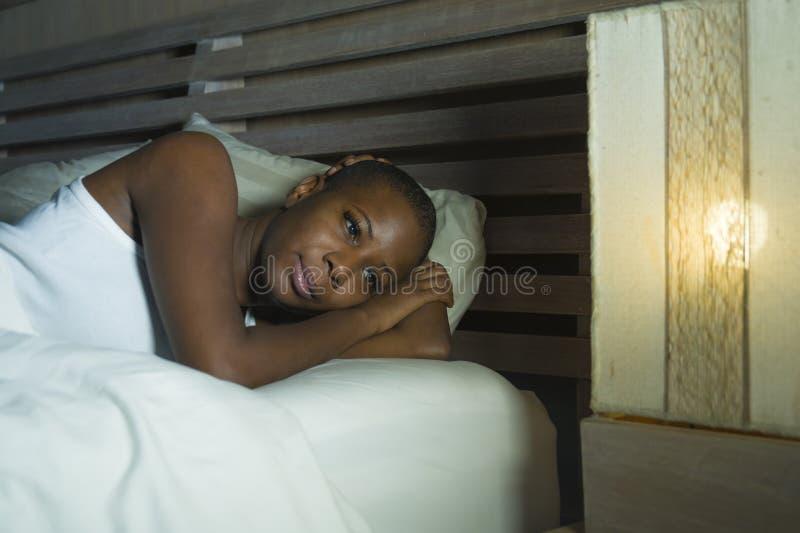 Het portret van de levensstijlnacht van het jonge droevige en beklemtoonde zwarte Afrikaanse Amerikaanse vrouw liggen bij bed het stock foto