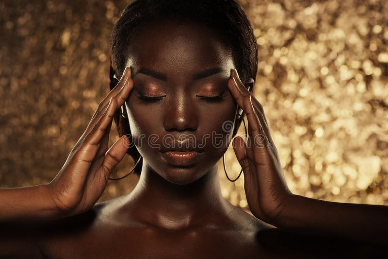 Het portret van de manierstudio van een buitengewoon mooi Afrikaans Amerikaans model met gesloten ogen over gouden achtergrond royalty-vrije stock fotografie