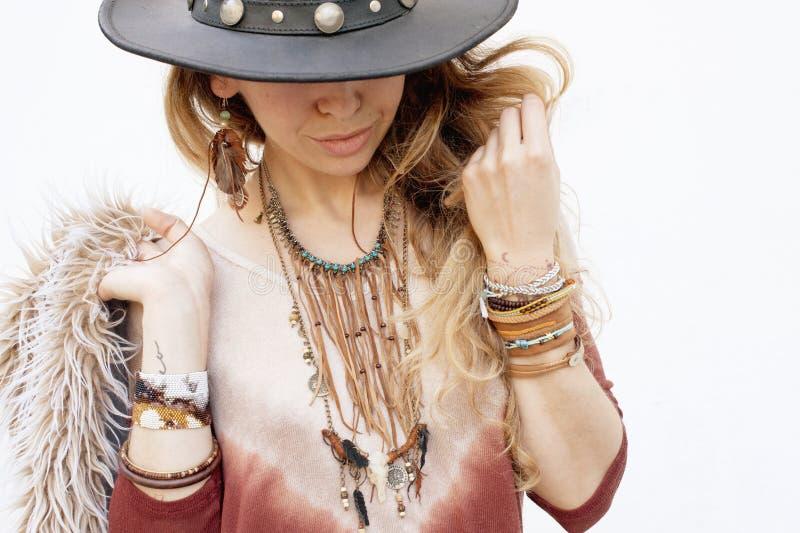 Het portret van de maniervrouw, handen met boho elegante armbanden, leerhalsband en hoed stock foto