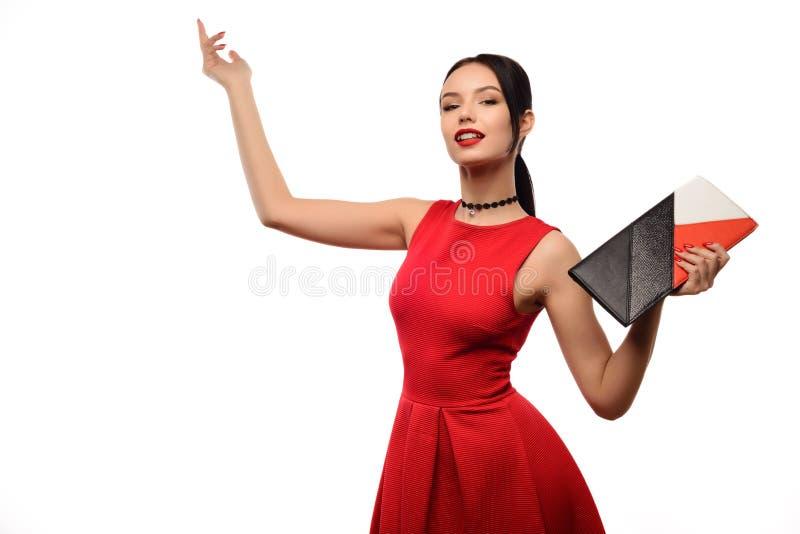 Het portret van de maniervrouw op wit wordt geïsoleerd dat De gelukkige zak van de meisjesgreep Rode Kleding Vrouwelijk mooi mode royalty-vrije stock afbeeldingen