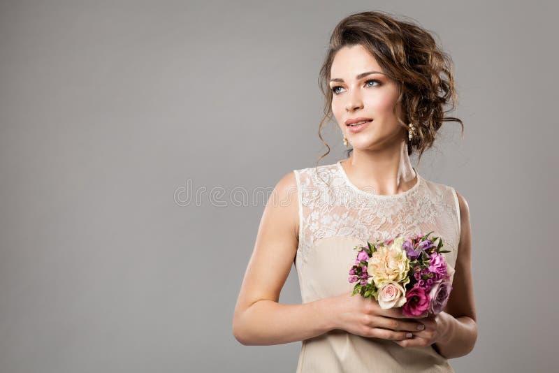Het Portret van de mannequinsschoonheid met Bloemenboeket, Mooi Vrouwen Bruids Make-up en Kapsel, Meisjesstudio schoot op grijs stock afbeeldingen