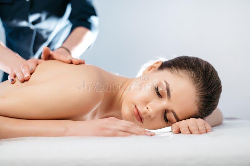Het portret van de mooie jonge vrouw met natuurlijke samenstelling rust tijdens massage in kuuroordsalon stock afbeeldingen