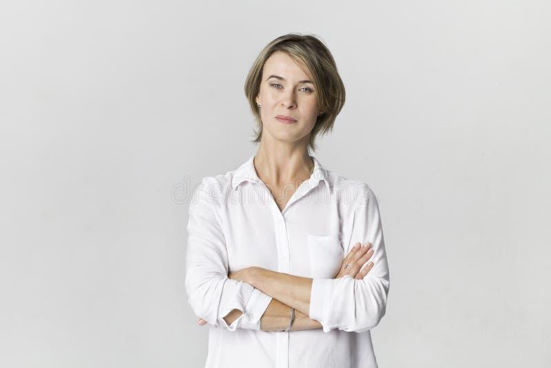 Het portret van de onderneemsterstudio Vertrouwensvrouw in wit die overhemd op wit wordt geïsoleerd royalty-vrije stock afbeeldingen