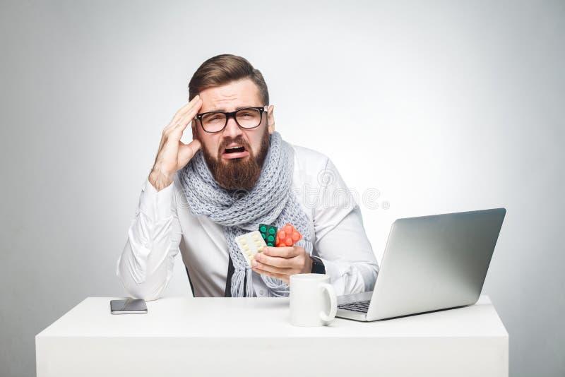 Het portret van de ongezonde vermoeide jonge mens in wit overhemd, de sjaal en de avondkleding zitten in bureau en moeten belangr stock fotografie