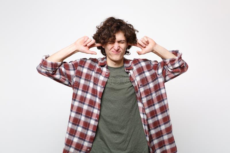 Het portret van de ontstemde jonge mens in vrijetijdskleding die ogen houden die sloot het behandelen van oren met vingers op wit royalty-vrije stock foto