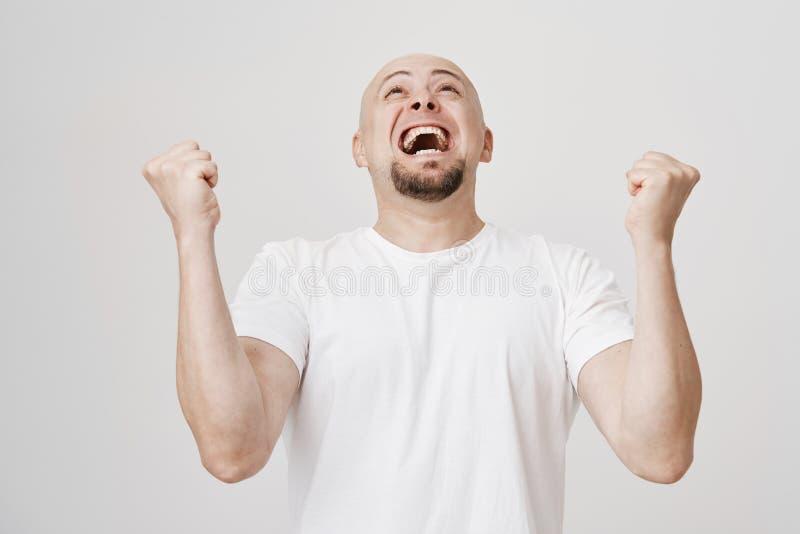 Het portret van de opgewekte vrolijke kale Europese mens met baard die achteruit terwijl het opheffen dient overwinningsgebaar in stock foto