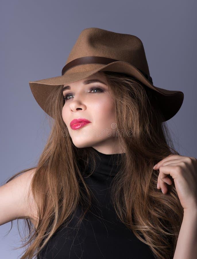 Het portret van de schoonheid Mooie jonge dame met een bruine hoed en zwarte kleren stock afbeelding