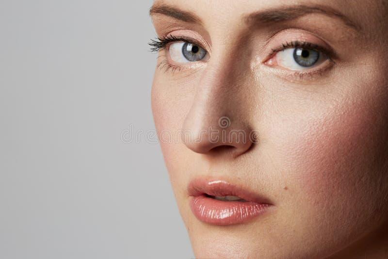 Het portret van de schoonheidsclose-up van een handsime jong wijfje met natuurlijke make-up over witte achtergrond De kosmetiek e royalty-vrije stock fotografie