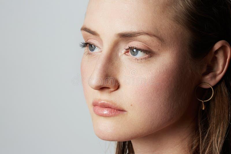 Het portret van de schoonheidsclose-up van een handsime jong wijfje met natuurlijke make-up over witte achtergrond De kosmetiek e royalty-vrije stock afbeeldingen