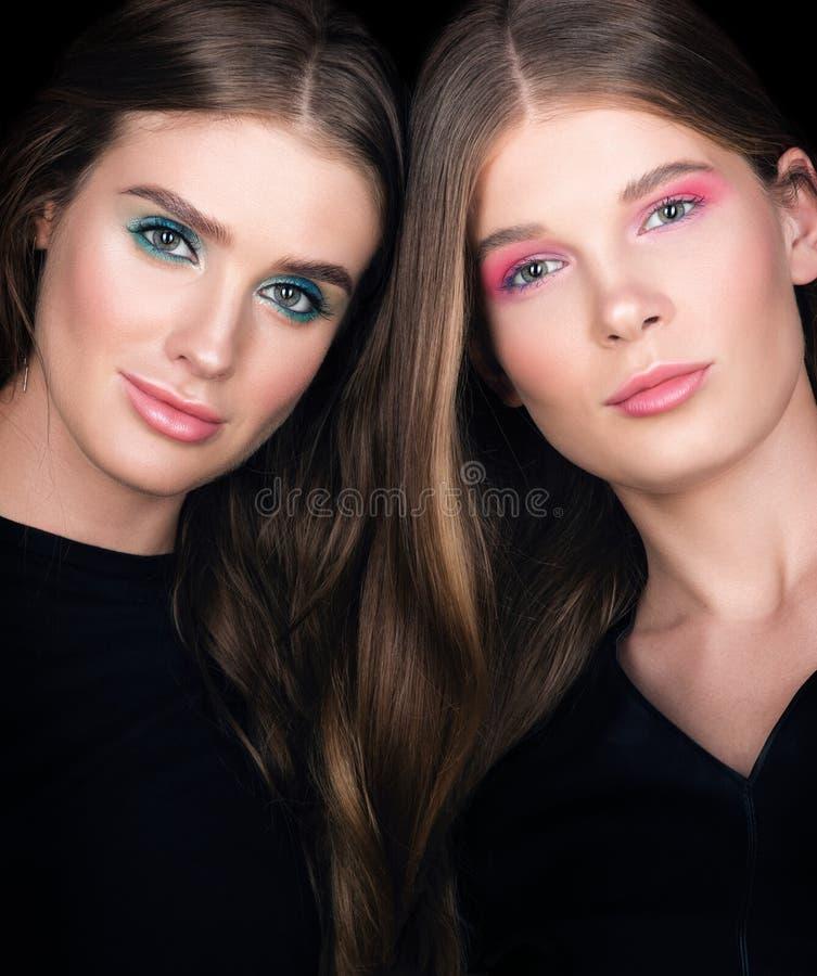 Het portret van de schoonheidsclose-up Twee mooie jonge vrouwen met geweven haar stock foto