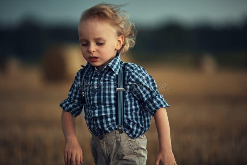 Het portret van de sluiting van een kleine blonde jongen die op het tarweveld loopt royalty-vrije stock afbeelding