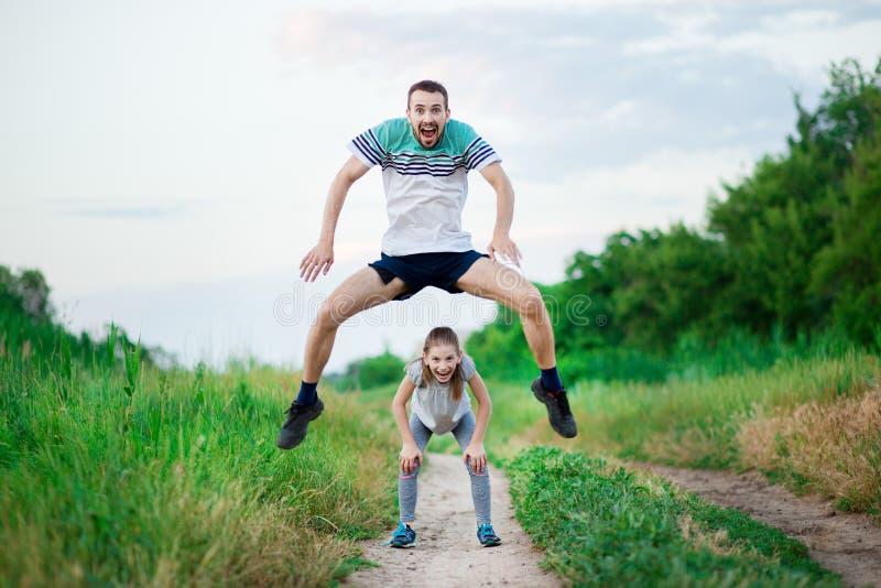 Het portret van de sportfamilie van knappe vader en zijn leuke kleine dochter spelen sprongkikker openlucht stock foto