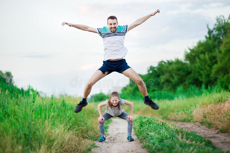 Het portret van de sportfamilie van knappe vader en zijn leuke kleine dochter spelen sprongkikker openlucht stock afbeeldingen