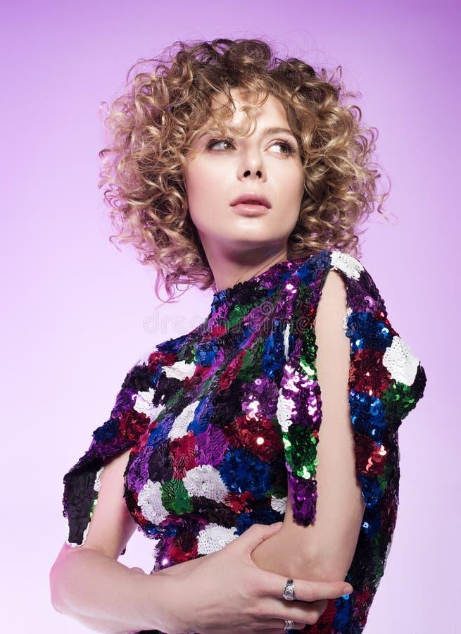 Het portret van de studiomanier van een jonge vrouw in kleedt zich sparkly Mooi krullend haar stock afbeeldingen