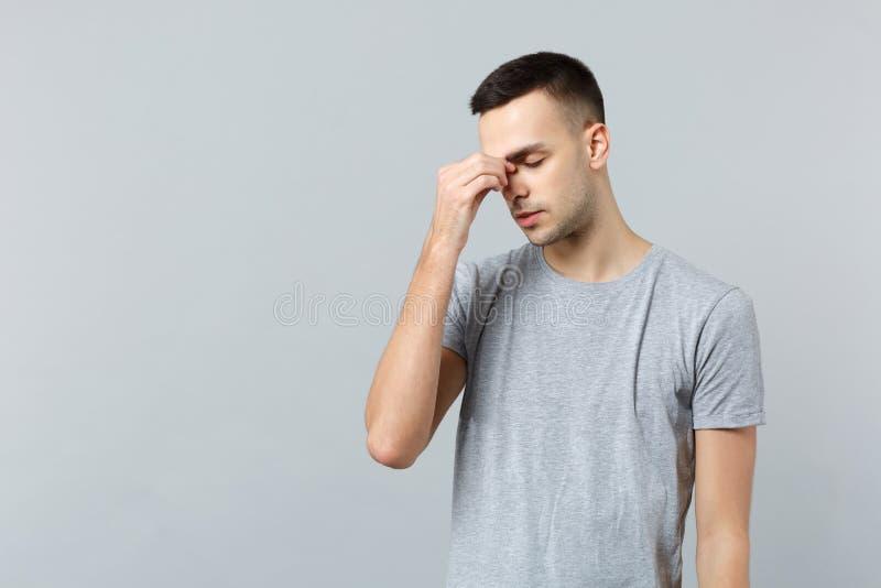Het portret van de uitgeputte jonge mens in vrijetijdskleding die ogen houden die sloot, zettend hand op neus op grijze muur word stock fotografie