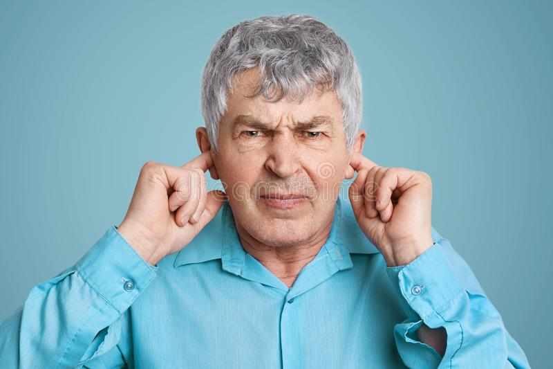 Het portret van de verstoorde geërgerde rijpe mens stopt oren met geklede vingers, in formeel overhemd, stelt tegen blauwe achter stock foto's