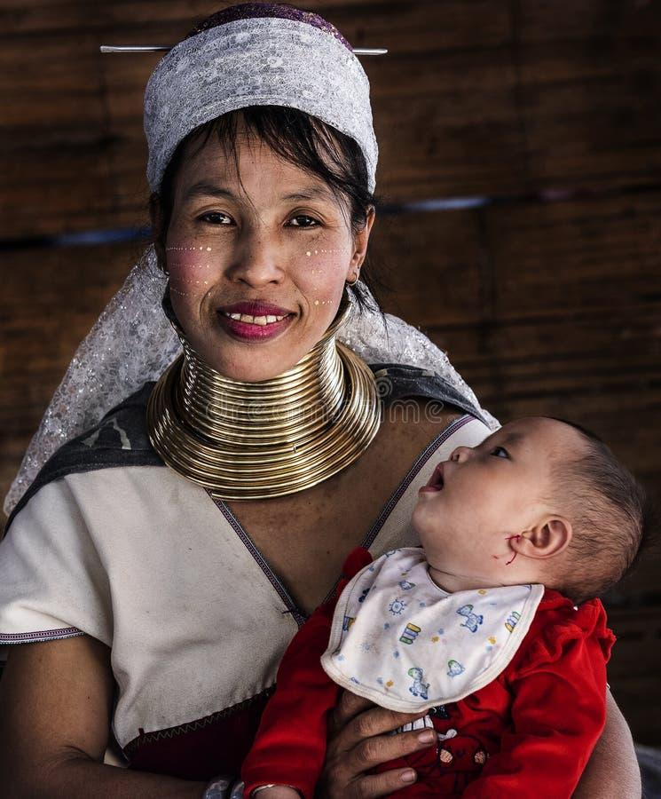 Het portret van de vrouw van de longneckstam en haar baby die haar moedergezicht bekijken in Chiang Mai sluiten halsdorp, Chiang  stock afbeeldingen