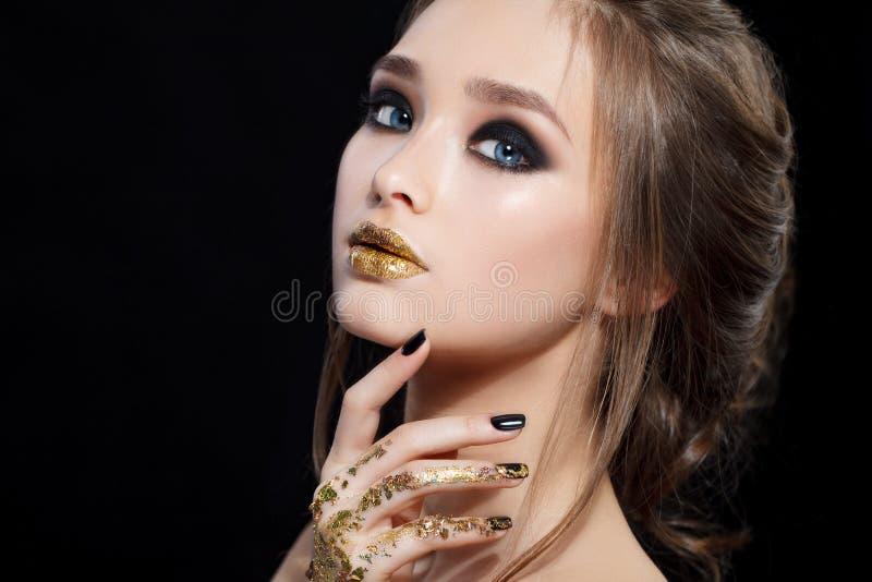 Het Portret van de Vrouw van de schoonheid De professionele Make-up en de Manicure met gouden folie schitteren, smokeyogen Zwarte stock fotografie