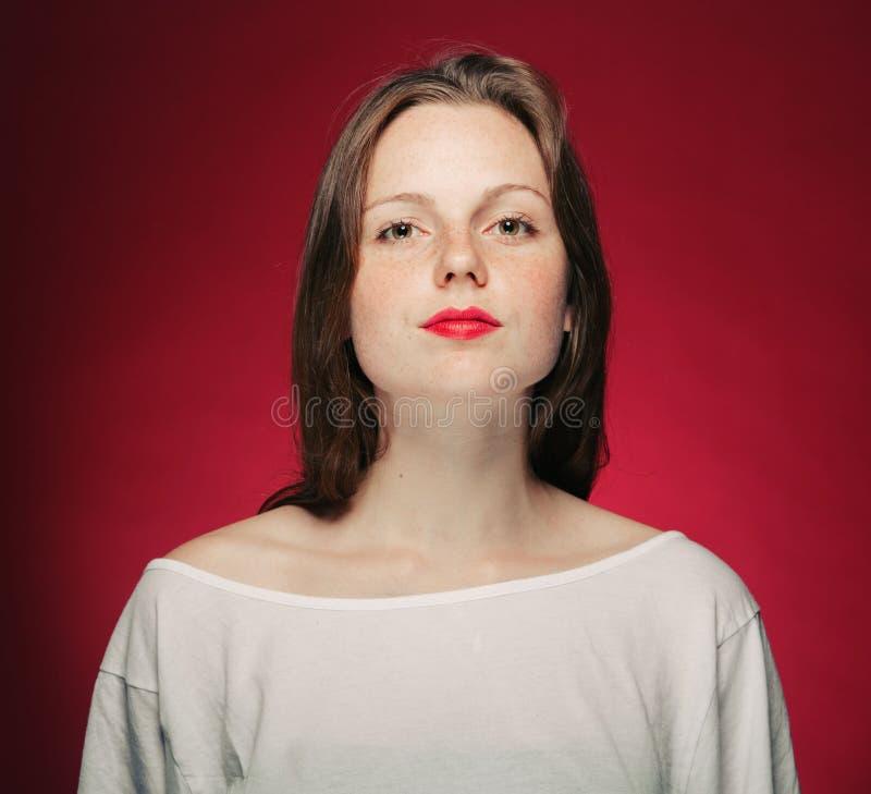 Het portret van de vrouwensproet op rood en roze kleurenachtergrond stock fotografie
