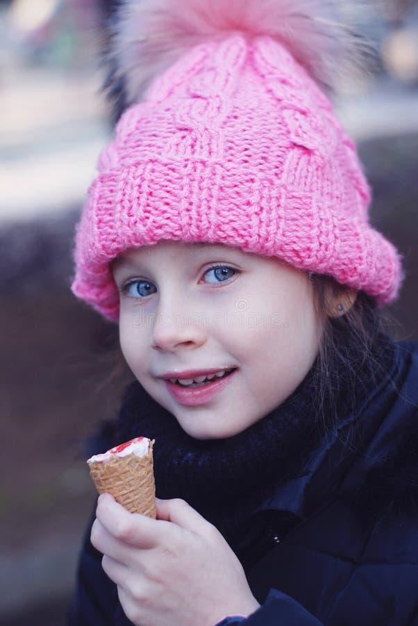 Het portret van de winter Mooi Glimlachend Meisje met Blauwe Ogen die het Roze Gebreide Roomijs van Hoedeneatting dragen, en bij  stock afbeeldingen