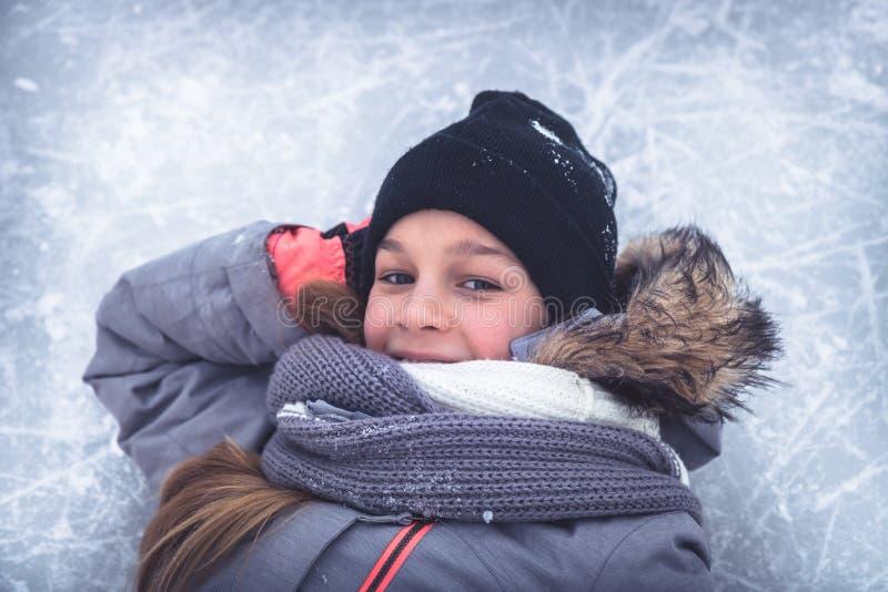 Het portret van het de winterkind op de achtergrond van het sneeuwijs op sneeuw het schaatsen ring tijdens de wintervakantie royalty-vrije stock foto's