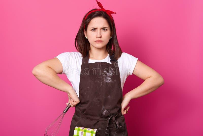 Het portret van donker die haired meisje in schort met bloem, t-shirt en rode haarband wordt bevuild, tribunes met handen op heup stock afbeeldingen